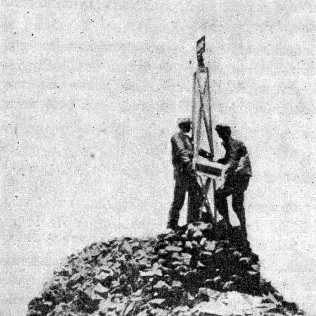 Photo of two men installing border monument on the summit of Zapaleri